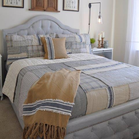Natural tones, classic patterns, and down-home fabrics like burlap create a rich-but-welcoming farmhouse bedroom.